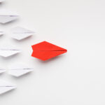 Focus Your culture - Opinion leadership concept. Red paper plane leading another ones, influencing the crowd, white background, top view with free space